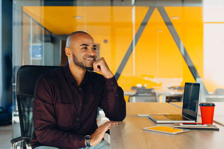 Have a nice working day. Confident young african american businessman working on laptop and talking on cell phone while sitting at his workplace in office
