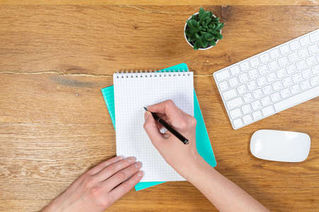 Workspace with keyboard, girl's hands, notepad, sketchbook on a wooden table, top view of an office desk table. Freelancer's place of work