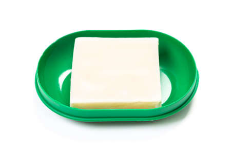 Soap in PLASTIC COLORED soap dish isolated on white background