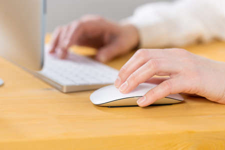 Close-up of young female hands pressing keyboard buttons and using a mouse. work from home. office. shopping