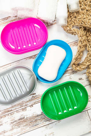 several plastic soap dishes and soap, on a wooden table. hygiene cleanliness travel concept