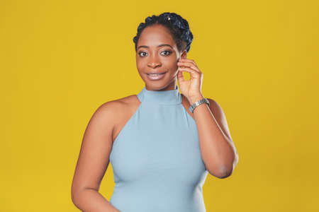 beautiful smiling african american girl in a blue dress, with hair-pigtails rejoices on a yellow background, look at the camera