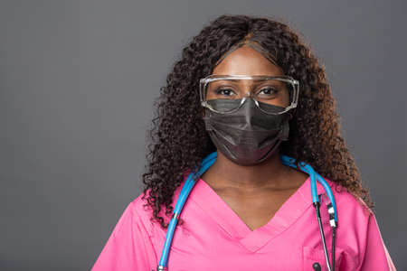 Young african american woman doctor in gloves mask and glasses on gray background smiling relaxed and cheerful. Success and optimism
