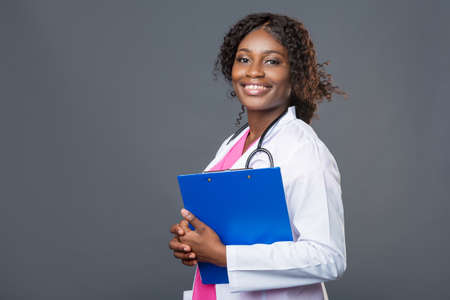Young nurse using a clipboard against a gray background. Portrait Of Female Nurse with a stethoscope in pink uniform