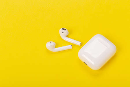 White wireless headphones with charging case on yellow background Фото со стока