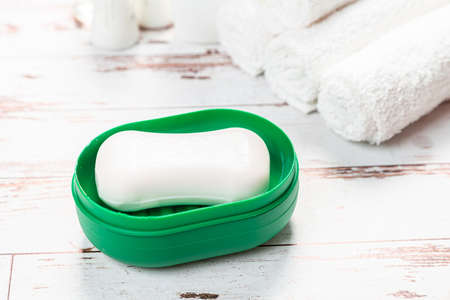 new soap on a green soap dish, on a white wooden background. hygiene concept