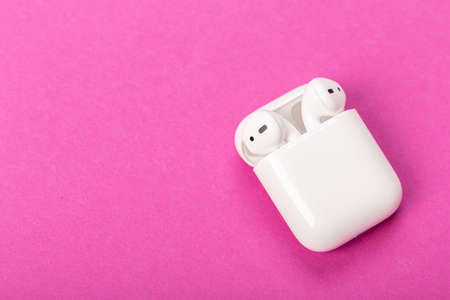 Modern wireless headphones with charging case on purple-pink background.