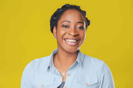 beautiful african american girl with curly hair braided in pigtails smiling happily on yellow background Фото со стока
