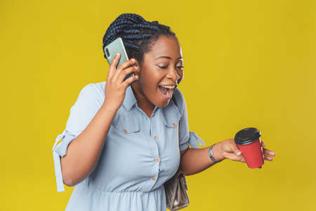 beautiful african american girl uses her mobile phone to chat happily smiling on yellow background