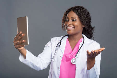 happy professional doctor black woman in white lab coat with stethoscope and tablet pc online consultations for her patients Фото со стока