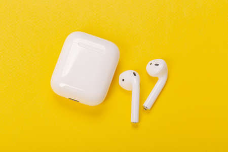Modern wireless earphones with charging case on a yellow background. The concept of modern technology.