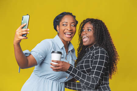 two friends beautiful african american girls take a selfie or video call with friends on a yellow background