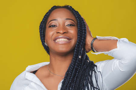 beautiful african american girl in a white shirt rejoices and smiles on a yellow background