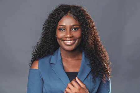 Young dark skinned woman in casual atmosphere looking at camera with copy space curly black hair on gray background Фото со стока