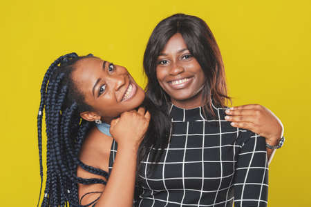 two beautiful afro american girls hugging and rejoicing and smiling on yellow background