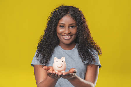 charming african american girl with dark hair with pink piggy bank in her hands on yellow background