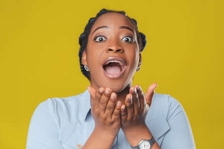 Beautiful african american girl with dark hair smiles happily and spreads her arms in different directions in surprise on a yellow background Фото со стока