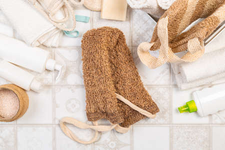 natural materials for bathroom accessories. bath sponges, washcloths, soap and towels on a light background. Фото со стока