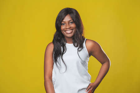 beautiful smiling african american girl with dark hair in a white shirt rejoices on a yellow background