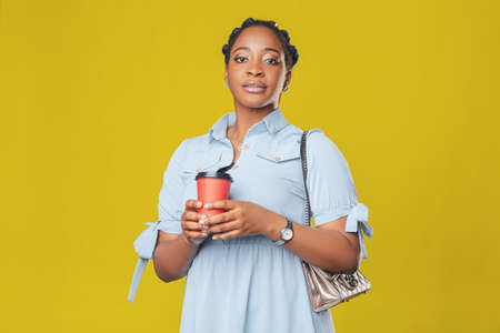 beautiful african american girl with takeaway coffee cup in hands on yellow background