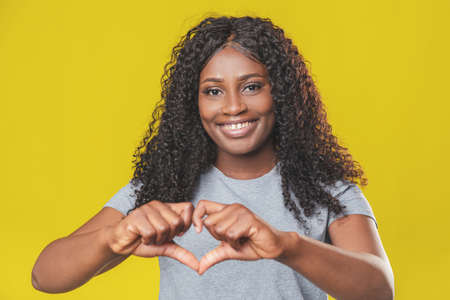 Beautiful african american girl with afro hairstyle smiling and showing with hands a heart sign with copy space on yellow background Фото со стока
