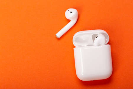 wireless headphones with charging case on orange background. The concept of modern technology. 스톡 콘텐츠