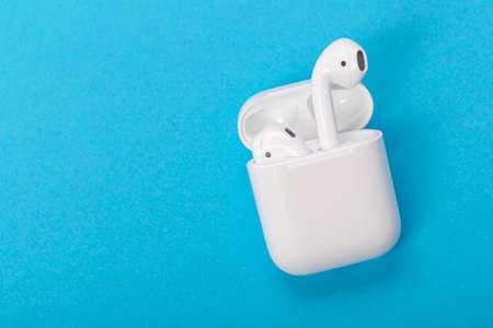 Modern wireless earphones with charging case on a blue background. The concept of modern technology.