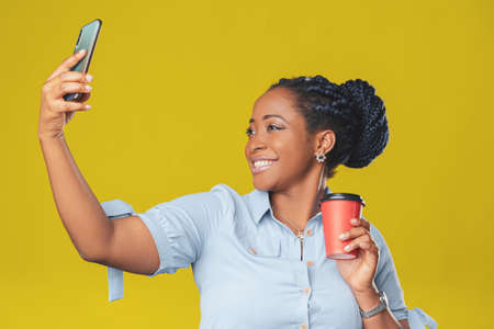beautiful african girl using her mobile phone for selfie smiling happily on yellow background