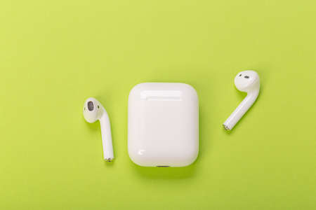 white wireless earphones with charging case on green background 스톡 콘텐츠