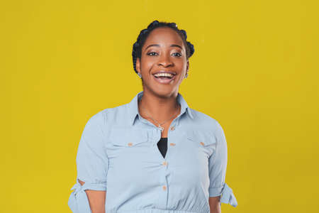 beautiful african american girl with curly hair braided in pigtails smiling happily on yellow background 스톡 콘텐츠