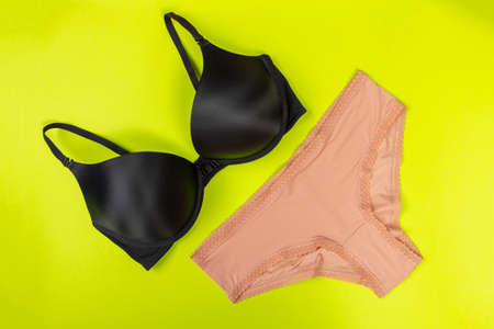 top view of fashionable bra and panties set on green background Female wardrobe, shopping concept. Underwear.