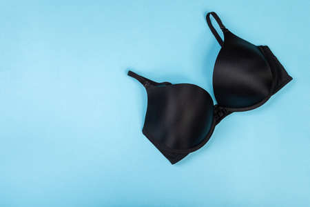 Top view of womens comfortable bra on turquoise background with copy space. Women's wardrobe, shopping concept. Underwear.