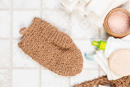 natural bathroom accessories, loofah glove mitten for the body, soap, cream, bath salt and towels on a light background. waste-free, environmentally friendly house