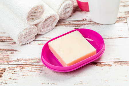soap on a pink plastic soap dish in the bathroom on a wooden table 스톡 콘텐츠