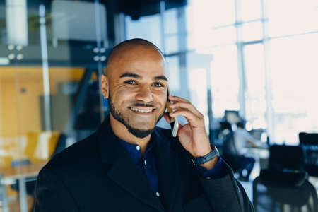 Happy african american businessman businesswoman with mobile phone in hands in modern office. Concept of young people work mobile devices.