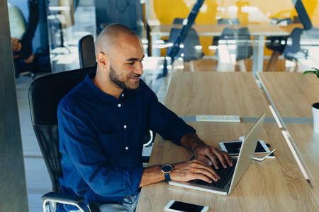 Happy african american businessman entrepreneur startup owner stand in modern office looking at camera, smiling young black designer creative person posing in work space