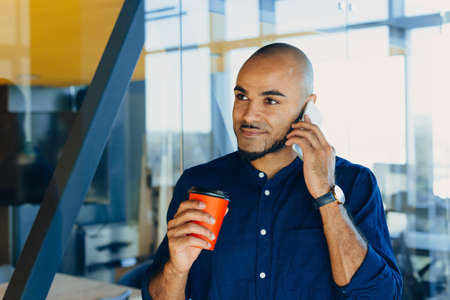 smiling young black designer creative man posing in workspace with a glass of coffee in his hands Фото со стока