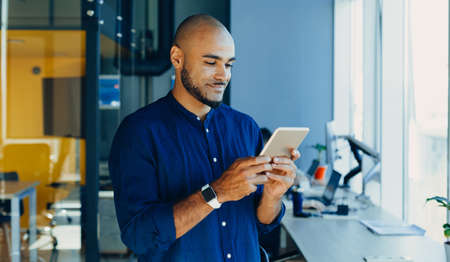 Happy african american businessman or or creative man with tablet in hands in modern free office, coworking