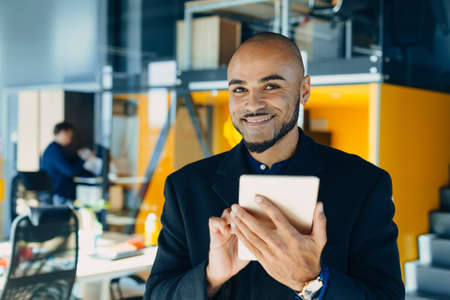 Happy african american businessman or designer or creative man with tablet in hands in modern office, business portrait Фото со стока