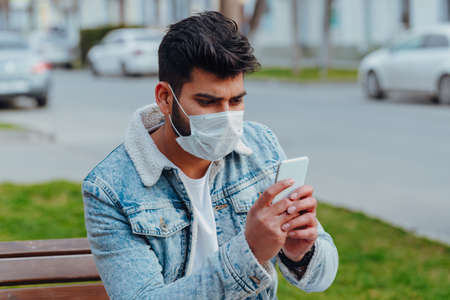 Fashionably dressed young Indian man in a medical mask walks on the street. hygienic mask to prevent infection, airborne respiratory illness such as flu or 2019-nCoV Фото со стока