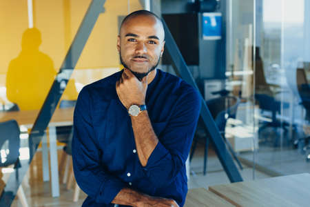 Handsome cheerful african american executive business man in office workspace. Concept of young people work in free schedule Фото со стока