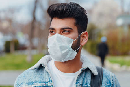 Fashionably dressed young Indian man in a medical mask walks on the street. hygienic mask to prevent infection, airborne respiratory illness.