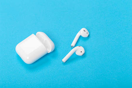 Modern wireless headphones with charging case on a blue background. The concept of modern technology, gadgets.