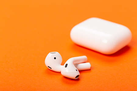 wireless headphones with charging case on orange background. The concept of modern technology. Фото со стока
