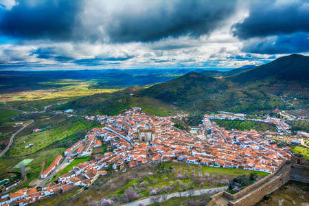 Landscape and castle of the city of Feria located in Extremadura, Spain. Landscape of a town and its castle with a beautiful valley and blue sky surrounded by nature.