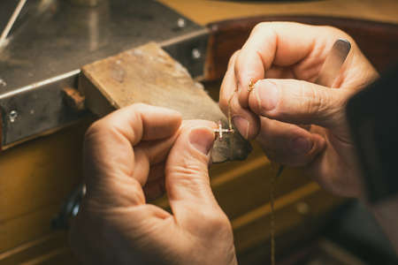 Hands of a craftsman jeweler working on jewelry. Goldsmith. Goldsmith workshop jewels and articles of work value