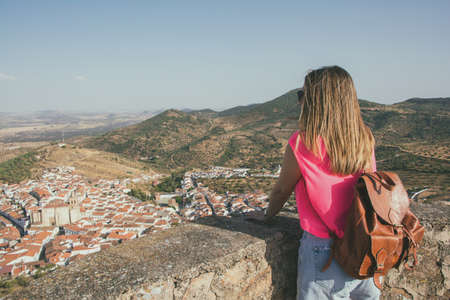 Feria town, located in Extremadura, Spain Stock photo of a rear view of a woman contemplating the landscape of a village surrounded by nature in a valley. Travels