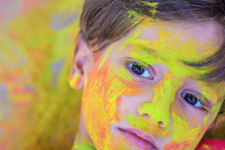 Portrait of child with colors in the face. Portrait of cute child drenched in colored powders during Holi Banque d'images