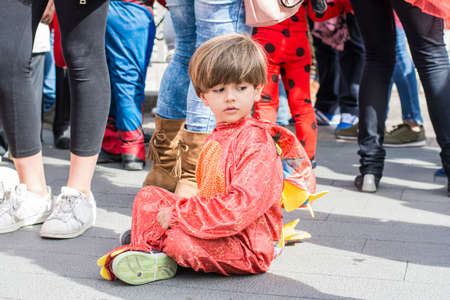 Boy In Dinosaur Costume Sitting On The Ground Surrounded By People. A little boy prepares for Halloween.