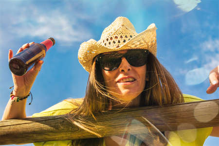 Happy Young Woman On The Beach Drinking Beer. Beautiful Happy Woman Making Funny And Crazy Gestures. Funny Woman, She Is Wearing A Cowboy Hat. Image Taken From Below. Happiness Concept.